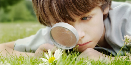 boy looking at daisy through magnifying glass