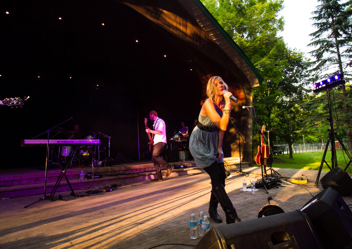 woman singing on a stage with a band behind her