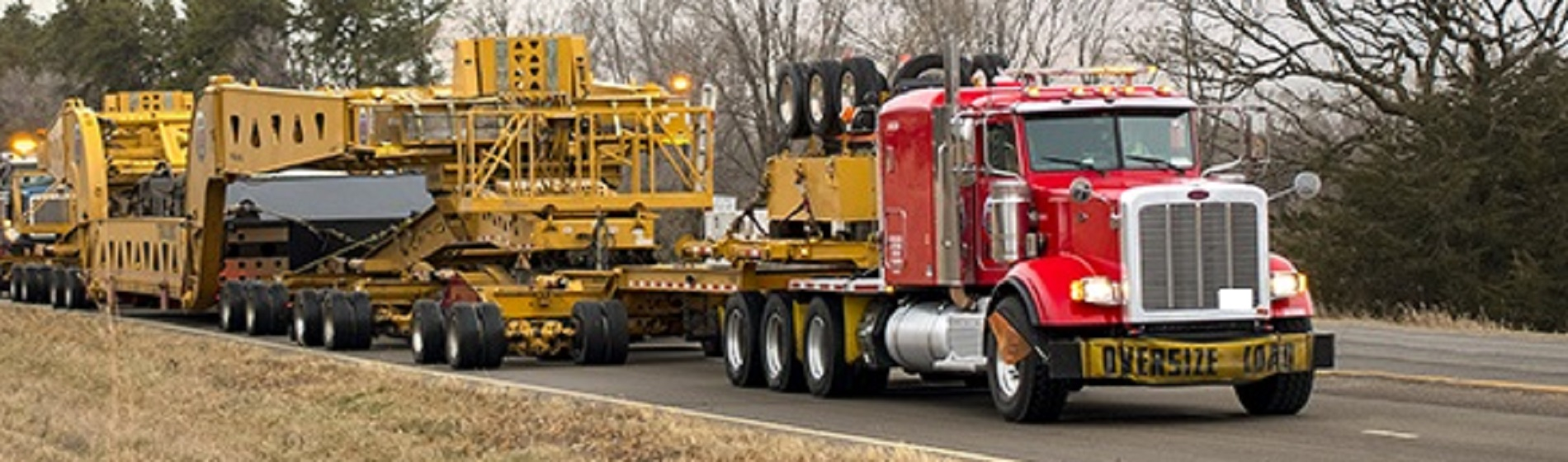 heavy equipment loaded on trailer hauled by truck